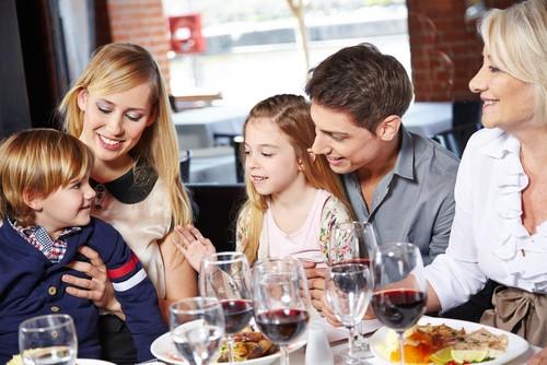 Família reunida ao redor de mesa.