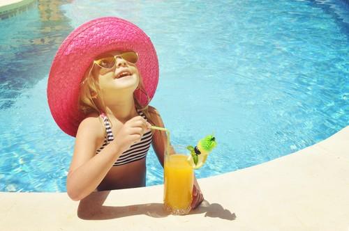 Menina em piscina bebe suco de laranja.